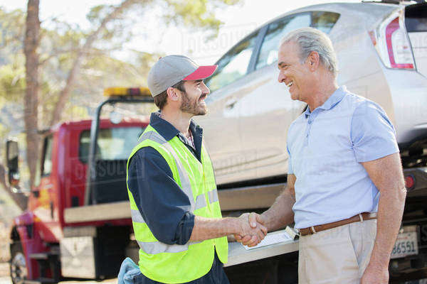 Roadside mechanic and man shaking hands Royalty-free stock photo