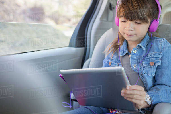 Girl with headphones using digital tablet in back seat of car Royalty-free stock photo