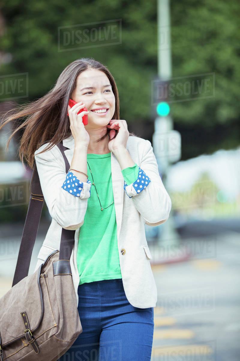 Happy Businesswoman Talking On Cell Phone In Crosswalk Stock Photo
