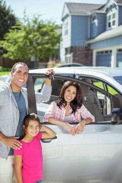 Portrait of smiling family at car in driveway Royalty-free stock photo