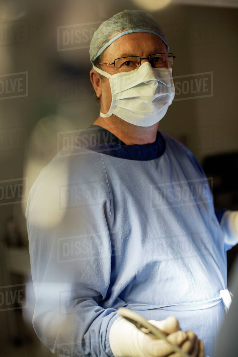 Surgeon wearing surgical mask, cap, gloves and gown in operating ...