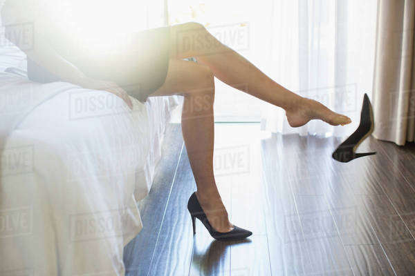Businesswoman kicking off her shoes in hotel room Royalty-free stock photo