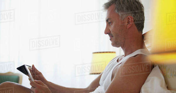 Man using digital tablet in bed Royalty-free stock photo