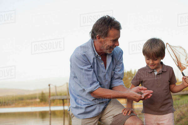 Smiling grandfather and grandson fishing at lakeside Royalty-free stock photo