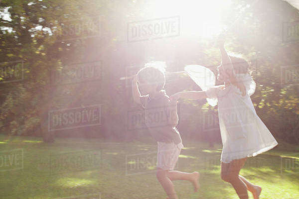 Boy and girl holding hands and running with butterfly nets in grass Royalty-free stock photo
