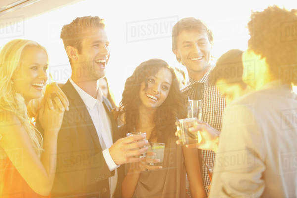 Smiling friends drinking cocktails on sunny balcony Royalty-free stock photo