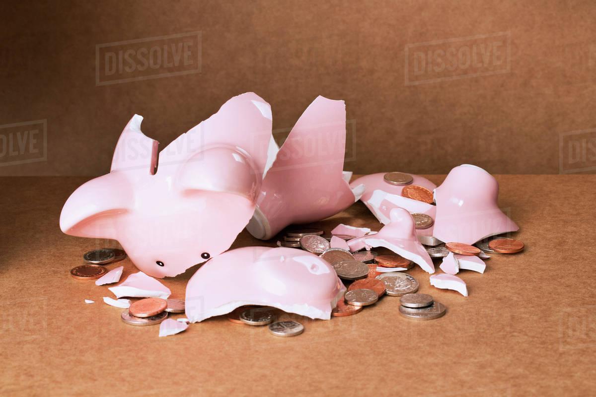 Broken piggy bank on counter - Stock Photo - Dissolve