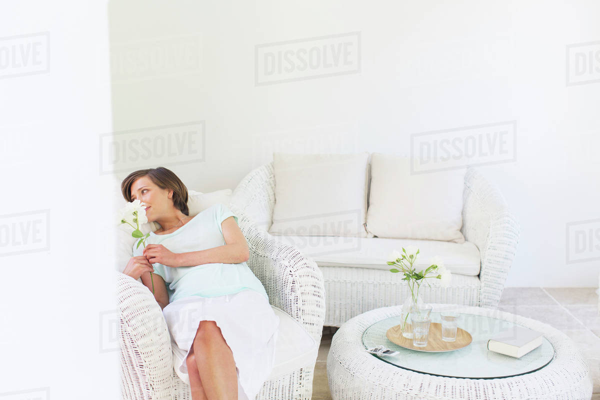 Woman Smelling Flowers In Wicker Chair In Living Room D985 21 038