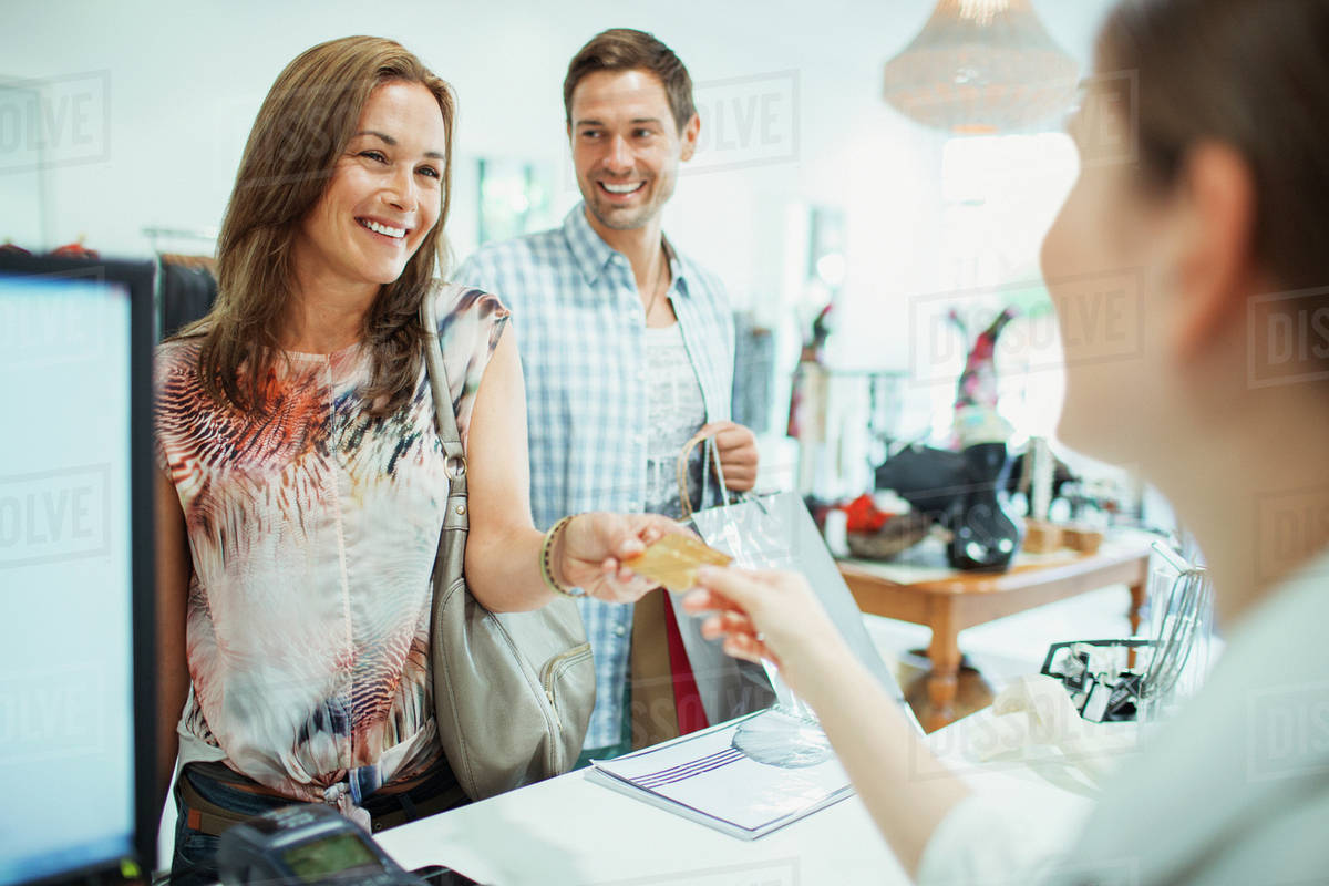 Couple Paying With Credit Card In Clothing Store Stock Photo