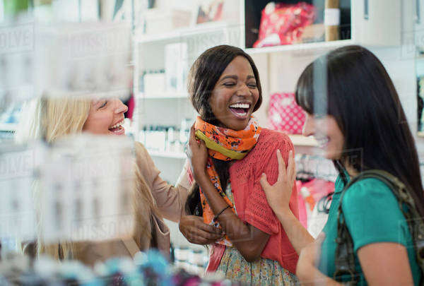 Women laughing together in clothing store Royalty-free stock photo