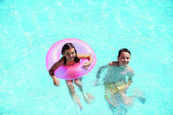 Portrait of brother and sister with pink inflatable ring in swimming pool Royalty-free stock photo