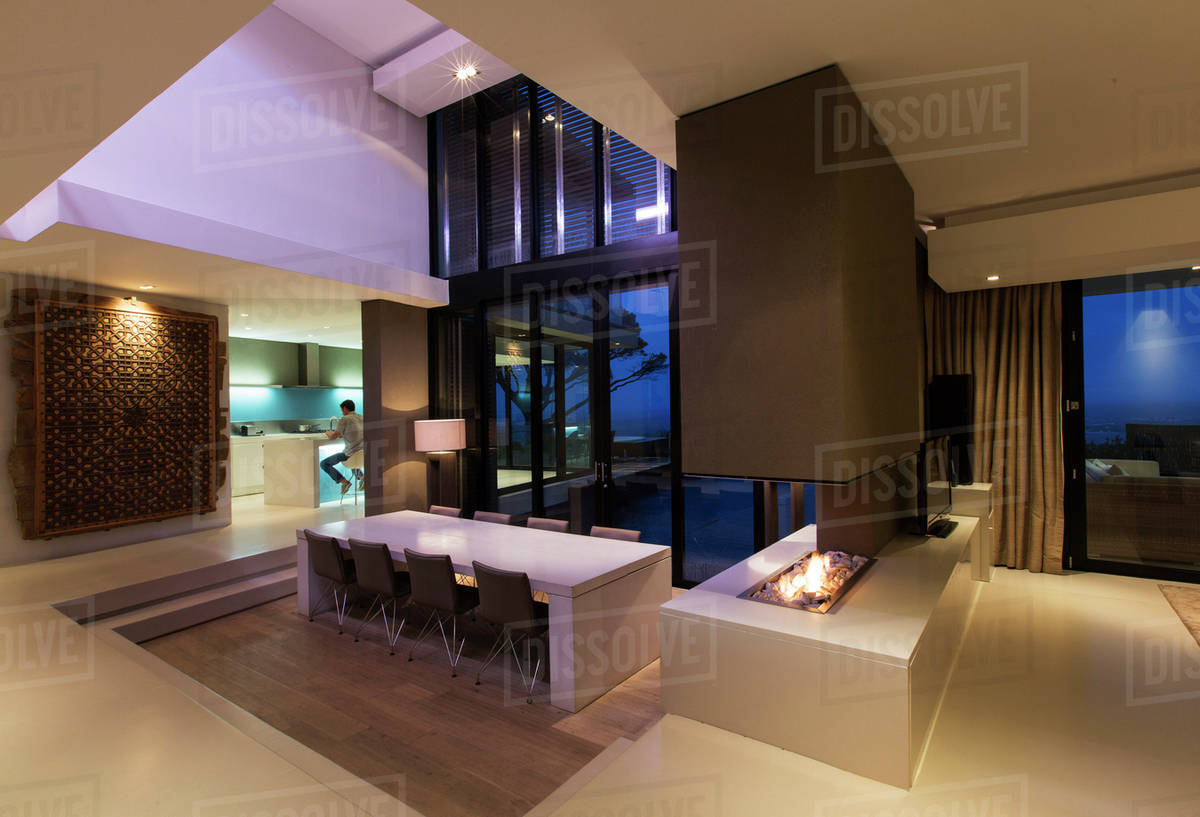 Dining area in modern house at night man in kitchen in background