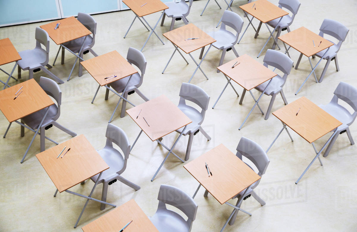 Elevated view of rows of desks and chairs in empty classroom stock photo