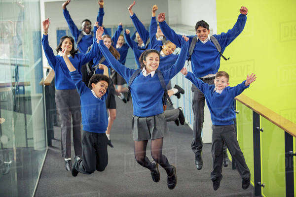 Enthusiastic high school students wearing school uniforms smiling and jumping in school corridor Royalty-free stock photo