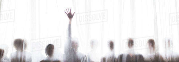 Silhouette of people behind transparent curtain, one person rising hand Royalty-free stock photo