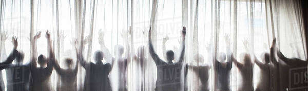 Silhouette of people raising hands behind transparent curtain Royalty-free stock photo