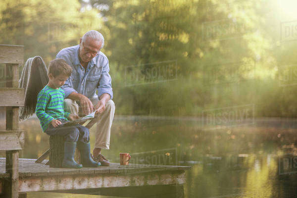 Grandfather and grandson reading at lake Royalty-free stock photo