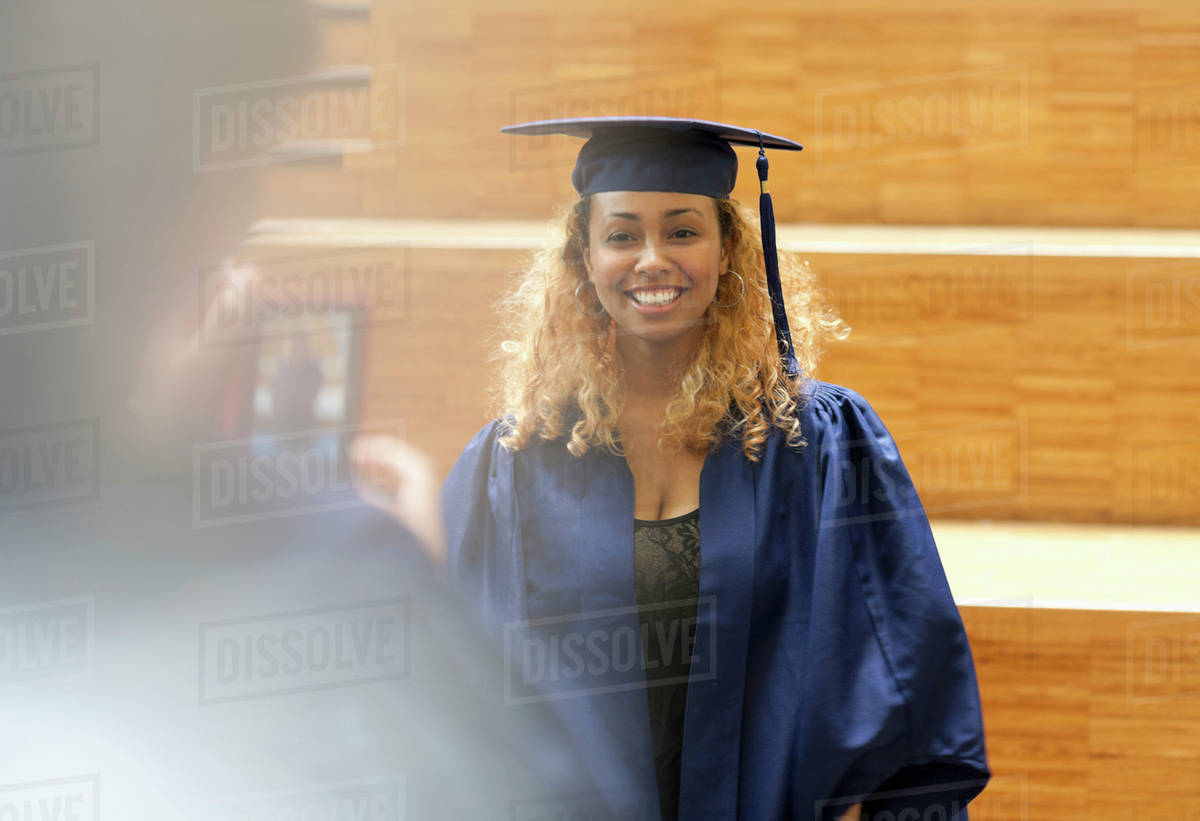Female student in graduation gown posing for picture in university ...