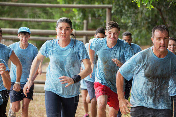 Team running in rain on boot camp obstacle course Royalty-free stock photo