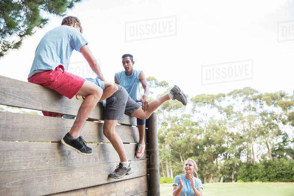 Teammates helping man over wall on boot camp obstacle course Royalty-free stock photo