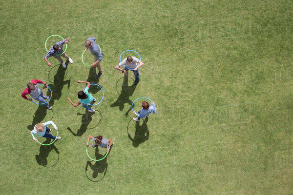 People spinning in plastic hoops in sunny grass Royalty-free stock photo