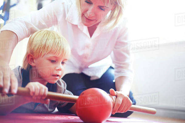 Physical therapist guiding boy rolling ball with stick Royalty-free stock photo
