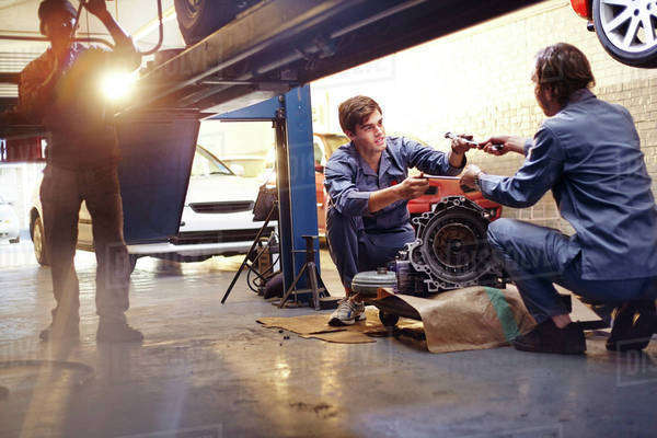 Mechanics discussing part in auto repair shop Royalty-free stock photo
