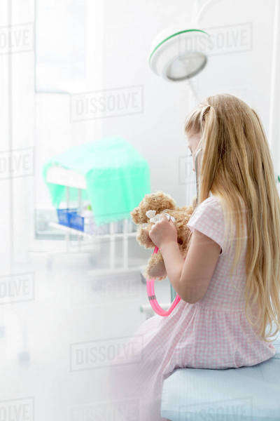 Girl using stethoscope on teddy bear in examination room Royalty-free stock photo