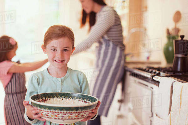 Portrait smiling girl baking holding bowl of flour in kitchen Royalty-free stock photo