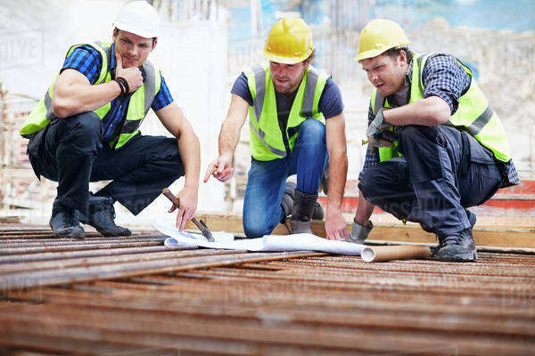 Construction workers and engineer reviewing blueprints at construction site Royalty-free stock photo