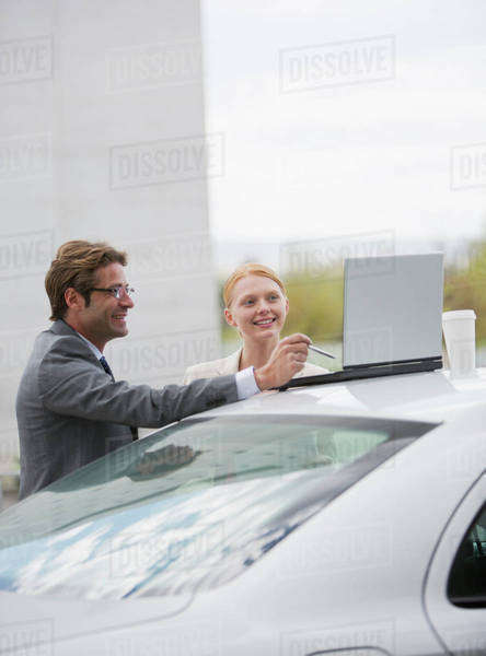 Smiling businessman and businesswoman using laptop on top of car Royalty-free stock photo