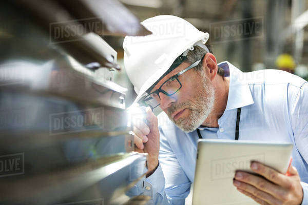 Focused engineer with digital tablet and flashlight examining part in factory Royalty-free stock photo