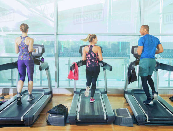 Man and women running on treadmills at gym Royalty-free stock photo