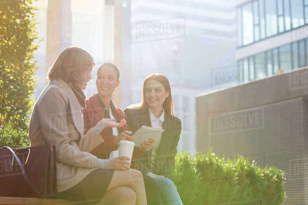 Smiling businesswomen with digital tablet drinking coffee outdoors Royalty-free stock photo