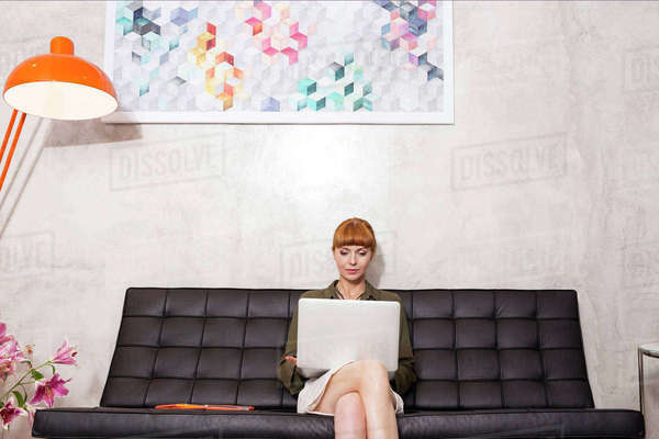 Creative businesswoman using laptop on sofa Royalty-free stock photo