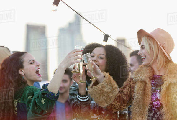 Enthusiastic young women toasting champagne glasses at rooftop party Royalty-free stock photo