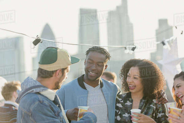 Young adult friends talking and drinking at rooftop party Royalty-free stock photo