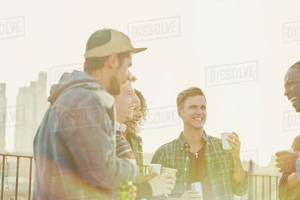 Young adult friends drinking and talking at rooftop party Royalty-free stock photo
