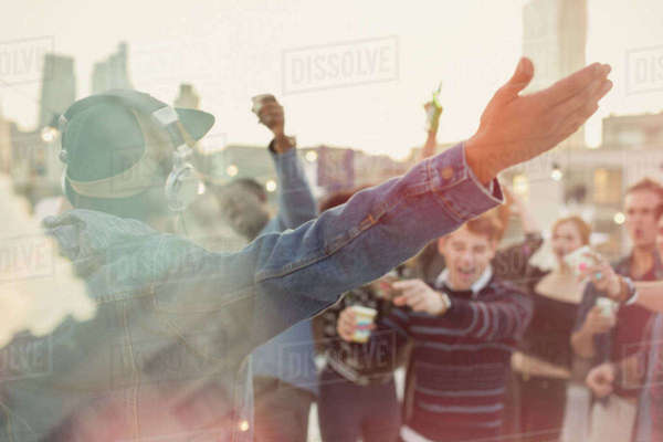 Young adult friends cheering for DJ at rooftop party Royalty-free stock photo
