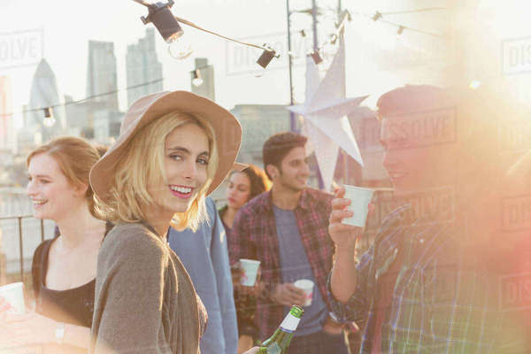 Portrait smiling young woman drinking beer at rooftop party Royalty-free stock photo