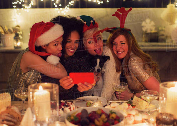 Playful young women with dog taking selfie at Christmas dinner Royalty-free stock photo