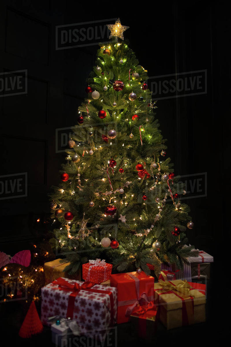 Dark Christmas.Illuminated Christmas Tree Surrounded By Gifts In Dark Room Stock Photo