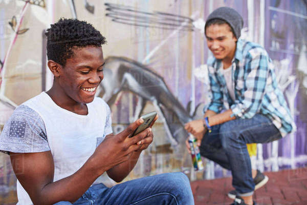Smiling teenage boys hanging out texting and spray painting graffiti on urban wall Royalty-free stock photo