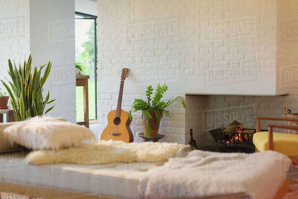 Guitar leaning near fireplace behind chaise in living room Royalty-free stock photo
