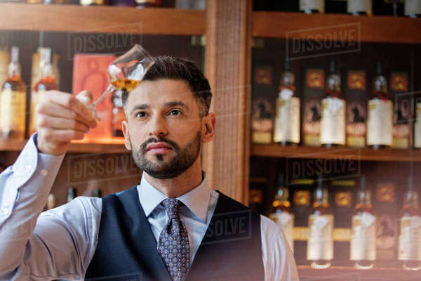 Serious well-dressed bartender examining whiskey Royalty-free stock photo