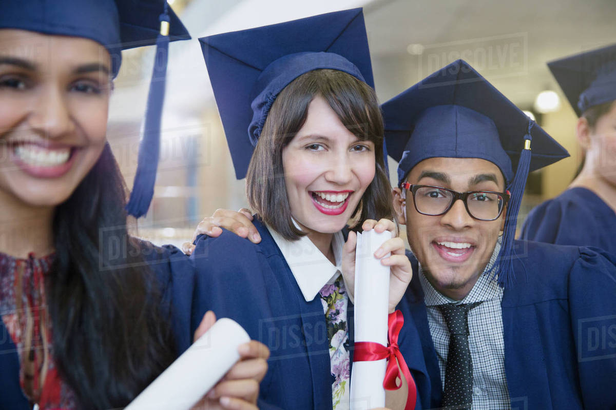 Portrait enthusiastic college graduates in cap and gown posing with ...