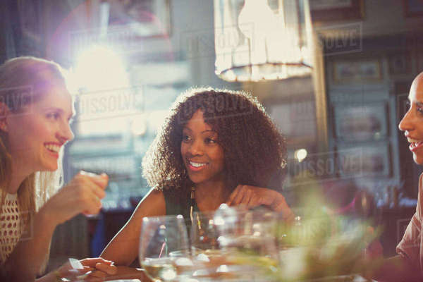 Smiling women friends dining and talking at restaurant table Royalty-free stock photo