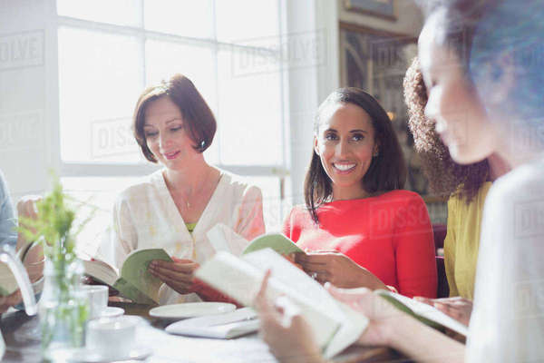 Women friends discussing book club book at restaurant table Royalty-free stock photo