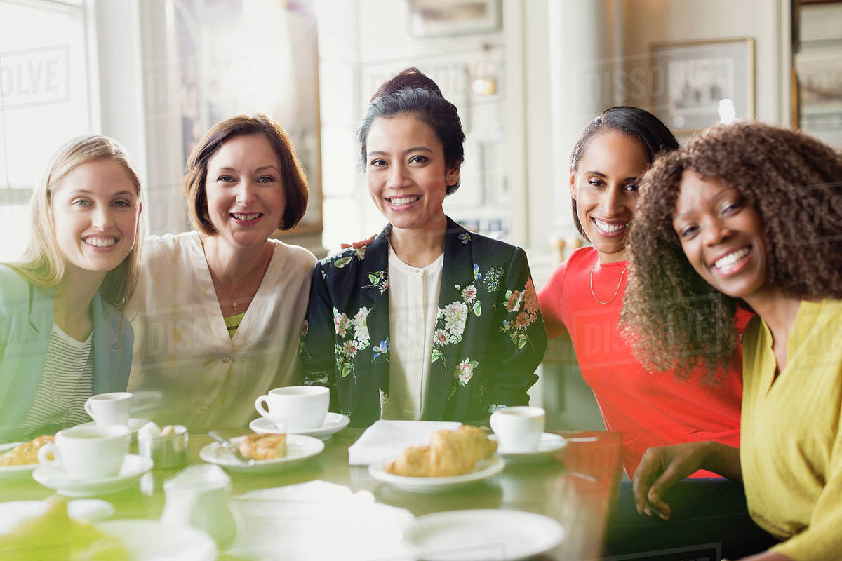 portrait smiling women friends drinking coffee at restaurant table