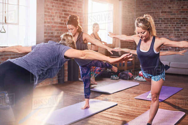 Women practicing yoga warrior 3 pose in exercise class gym studio Royalty-free stock photo